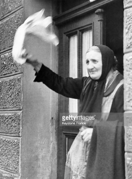 Une vieille femme debout à la porte de sa maison les larmes dans les yeux secoue un chiffon blanc alors que la 9e Armée américaine est entrée dans...
