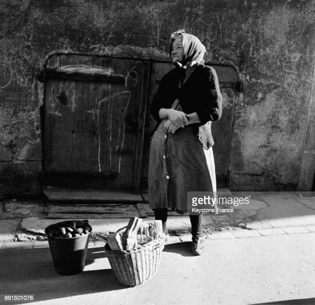 Une vieille femme vendant ses propres légumes dans la rue à Dole France le 2 mars 1953