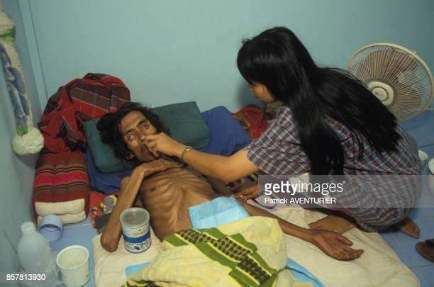Une volontaire soigne un malade peu avant sa mort en juin 1994 en Thailande