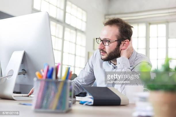 Uneasy young businessman with eyeglasses at workplace
