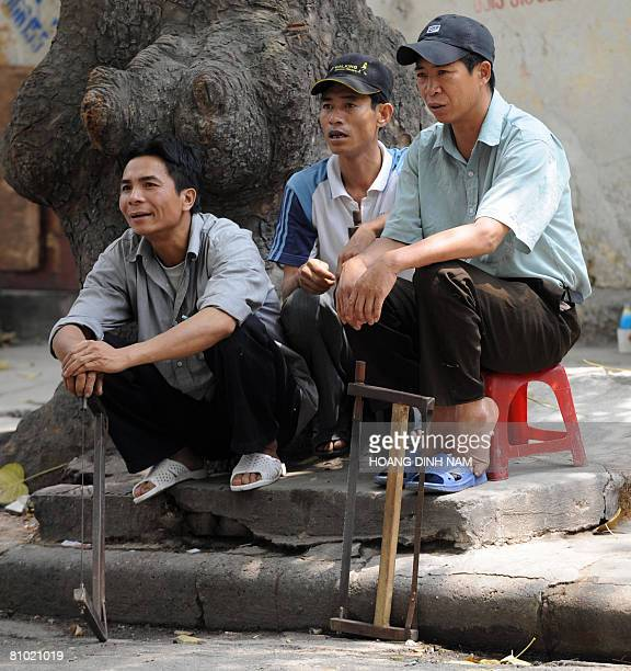 Unemployed carpenters sit as they wait to be hired for daily jobs on the pavement of a street in downtown Hanoi on May 8 2008 The Vietnamese...