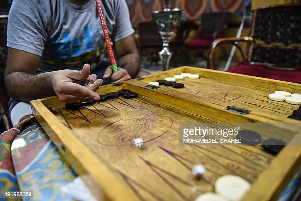 A unemployed Egyptian man plays backgammon at a cafe in the capital Cairo on October 8 2015 North Africa and Middle East regions still have the...