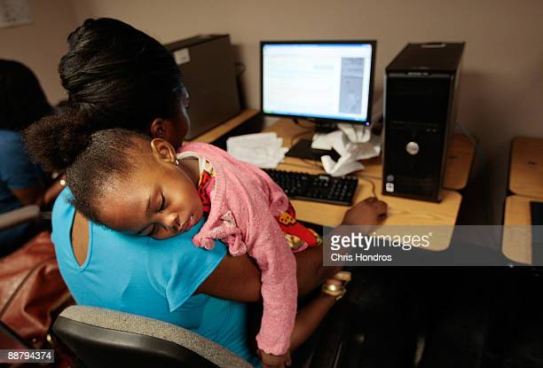 Unemployed mother Janet Francis of Brooklyn looks for a job while her daughter Kayli sleeps on her shoulder at the New York State Labor Department's...