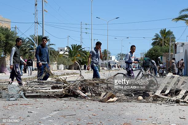 Unemployed newlygraduated Tunisian youths walk past a makeshift road block in the locality of Laataya on the island of Kerkennah on April 15 2016...