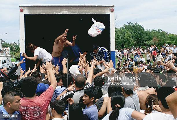 Unemployed people distribute free food provided by the 'Coto' supermarket in Ciudadela suburb of Buenos Aires 19 December 2001 after the supermarket...