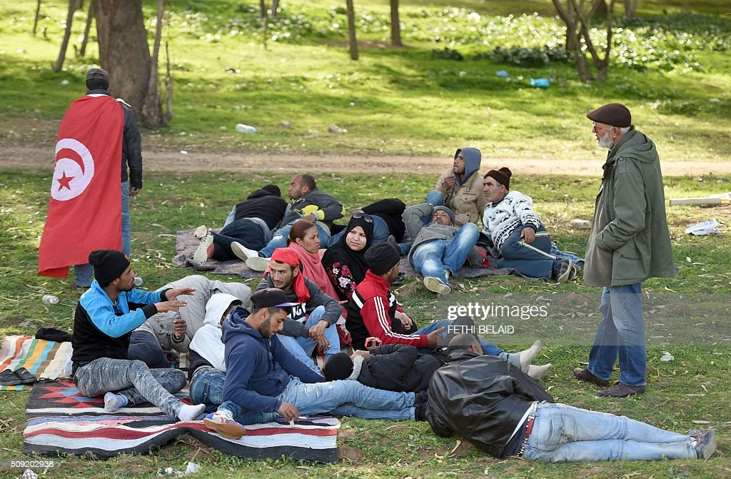 Unemployed Tunisians sit at el-Mourouj park after took part in a 400 kilometres march from the city of Gafsa to Tunis to demand work, on February 9, 2016, in the Tunisian capital. While Tunisia is hailed as a rare success story of the Arab Spring uprisings, authorities have failed to redress the economy or resolve the problems of social exclusion and regional inequalities. Apart from the political turmoil of the past five years which has handicapped the economy, the North African country also faces jihadist violence that has devastated its vital tourism industry. BELAID