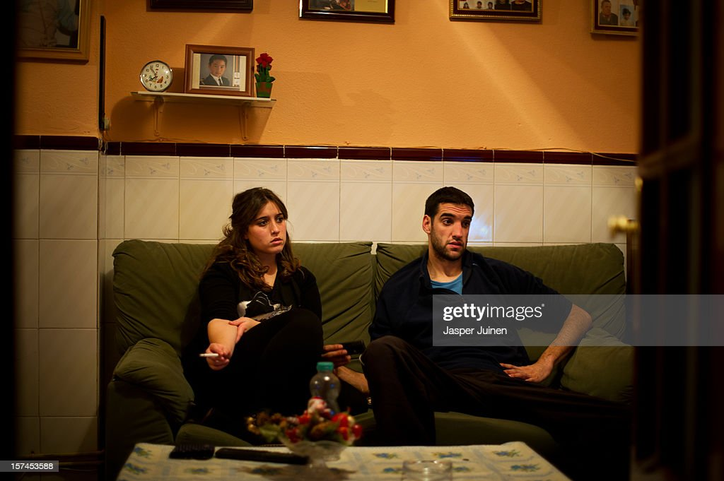Unemployed twenty-year old Maria Regina Fernandez (L) spends the night watching television with her boyfriend, who does also not hold a job, instead of going out to the cinema or the villages bars and cafeterias, at their grandmothers home on November 29, 2012 in Villacanas, Spain. During the boom years, where in its peak Spain built some 800,000 houses a year accompanied by the manufacturing of millions of wooden doors, the people of Villacanas were part of Spain's middle class enjoying high wages and permanent jobs. During the construction boom years the majority of the doors used within these new developments were made in this small industrial town. Approximately seven million doors a year were once assembled here and the factories employed a workforce of almost 5700 people, but the town is now left almost desolate with the Villacanas industrial park now empty and redundant. With Spain in the grip of recession and the housing bubble burst, Villacanas is typical of many former buoyant industrial Spanish towns now struggling with huge unemployment problems.