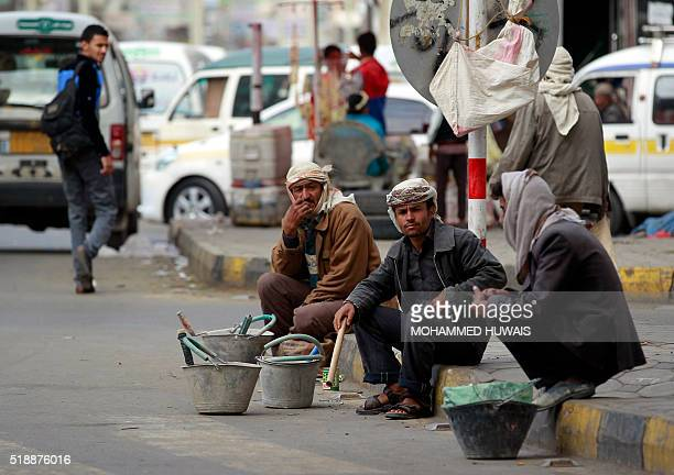 Unemployed Yemeni manual laborers wait for work offers on a sidewalk in Sanaa on April 3 2016 / AFP / MOHAMMED HUWAIS