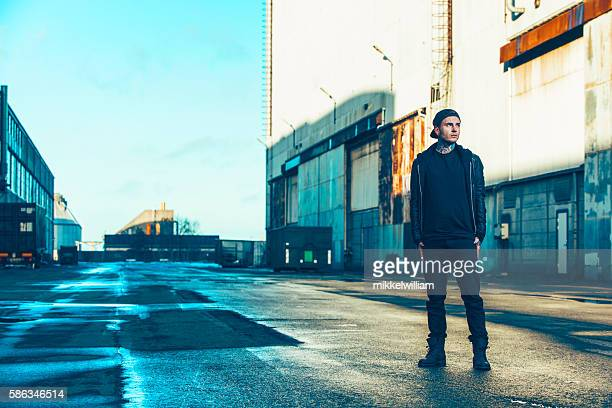 Unemployed young adult stands alone outside in industrial area