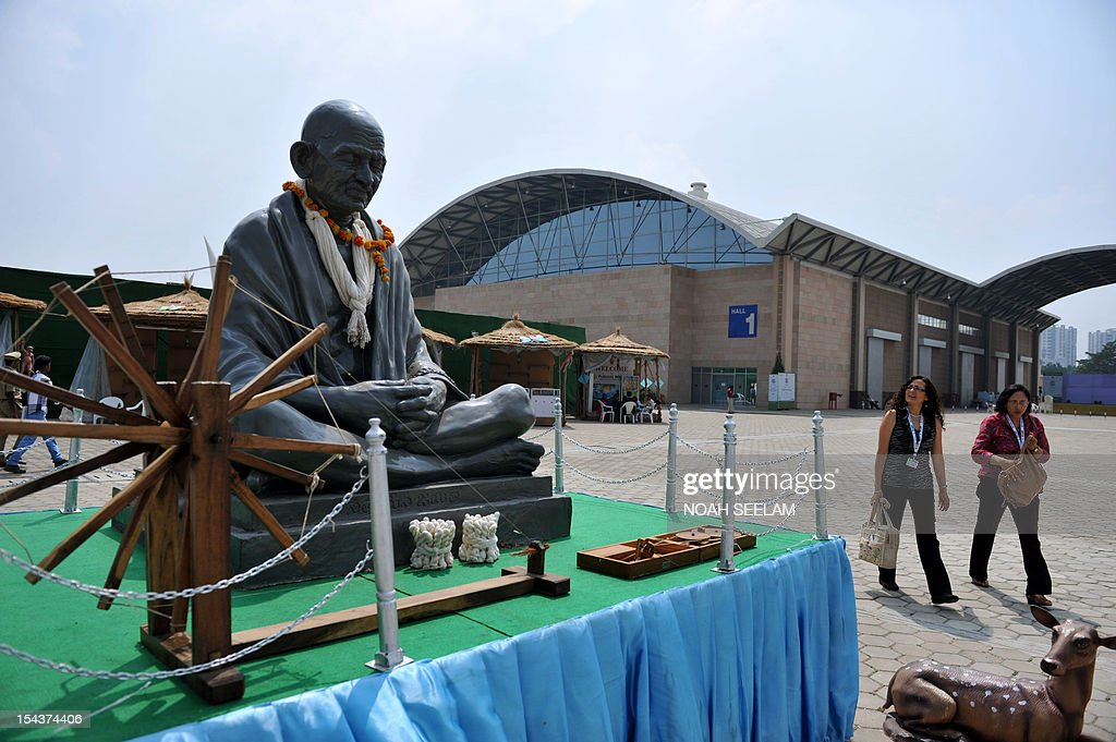 UN-environment-biodiversity-agriculture-India-cotton,FOCUS by Mariette le Roux Delegates walk past a statue of Indian freedom icon Mahatma Gandhi displayed at an exhibition centre at the Hyderabad International Convention Centre (HICC) Convention on Biodiversity(CBD) conference in Hyderabad on October 19, 2012. When Indian icon Mahatma Gandhi took up the baton for home-grown cotton a century ago, he may not have realised the devastating impact its cultivation would have on the land he so loved. Cotton is a thirsty plant and parts of India drought-prone. But the intensive farming process for cotton leaches the soil and requires high pesticide and fertiliser use that pollutes further downstream. AFP PHOTO/Noah SEELAM