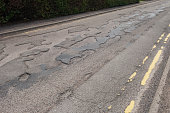 Uneven and weathered tarmac road surface - Scotland, UK.