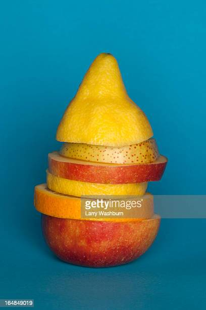 Uneven slices of different fruit stacked to comprise the shape of a piece of fruit