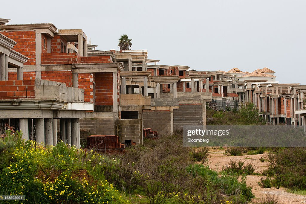 Unfinished apartment blocks stand on a hillside overlooking the marina area at Albufeira, Algarve region, Portugal, on Saturday, March 9, 2013. The tourism and real estate sector's recovery is crucial for Portugal's economy, which the government projects will return to growth next year, after shrinking an estimated 1 percent in 2013 and 3 percent in 2012. Photographer: Mario Proenca/Bloomberg via Getty Images