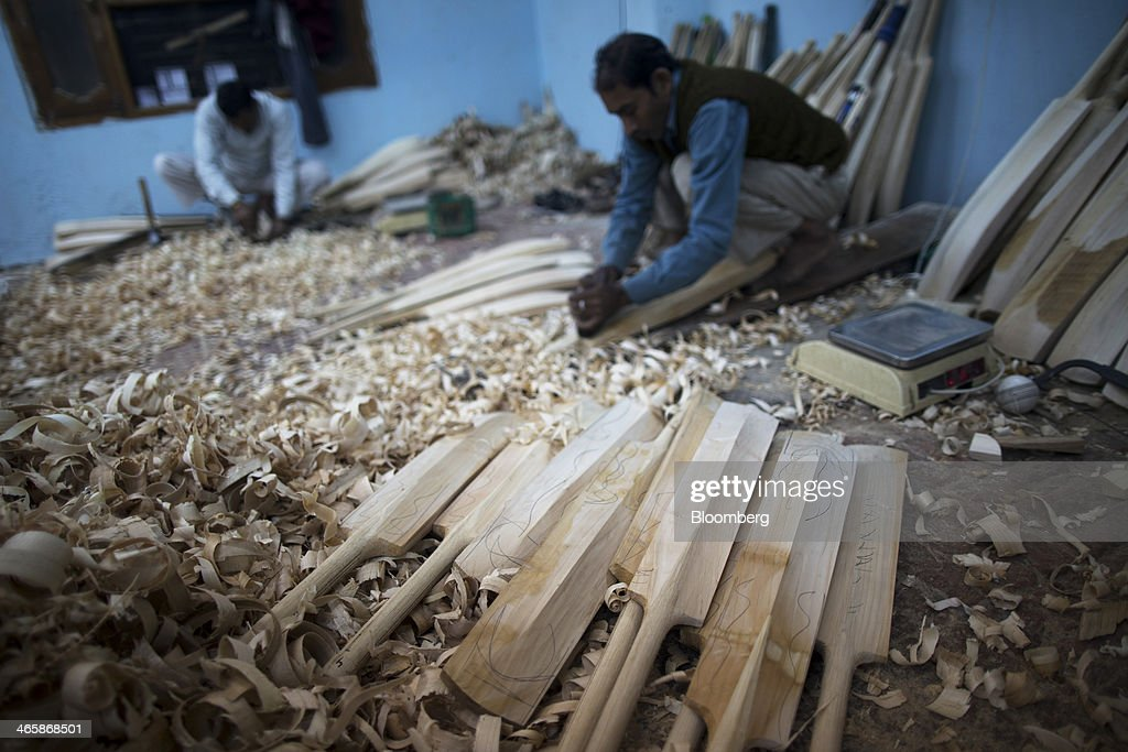 Unfinished cricket bats sit amongst wooden shavings as employees use hand planes to shape cricket bats at a Stanford Cricket Industries factory in Meerut, Uttar Pradesh, India, on Wednesday, Jan. 29, 2014. The Indian Premier League (IPL), the worlds richest cricket competition, auction for IPL 2014 is scheduled to begin on Feb. 12 with the seasons first match to be played on April 8. Photographer: Prashanth Vishwanathan/Bloomberg via Getty Images