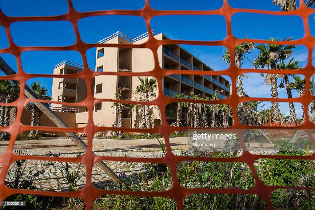 Unfinished luxury apartment blocks are seen through plastic fencing at the closed Herdade dos Salgados Resort, operated by ECS Capital, near Albufeira, Algarve region, Portugal, on Saturday, March 9, 2013. The tourism and real estate sector's recovery is crucial for Portugal's economy, which the government projects will return to growth next year, after shrinking an estimated 1 percent in 2013 and 3 percent in 2012. Photographer: Mario Proenca/Bloomberg via Getty Images