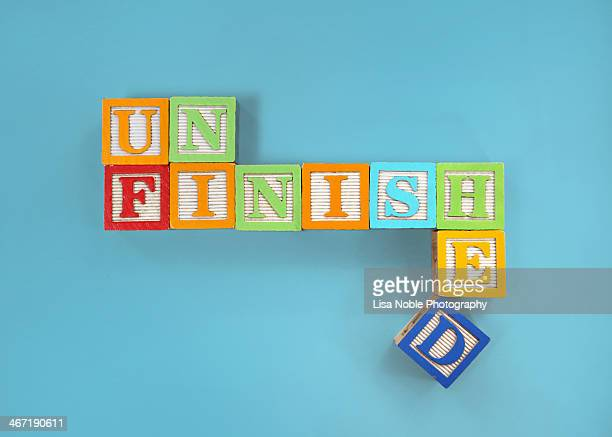 'Unfinished' spelled with children's wooden blocks