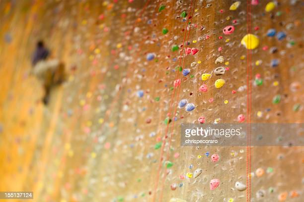 Unfocused man climbing an indoor rock climbing wall