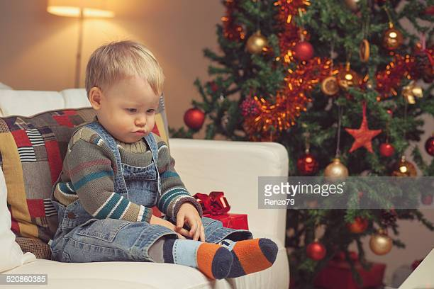 unhappy baby boy with present in christmas