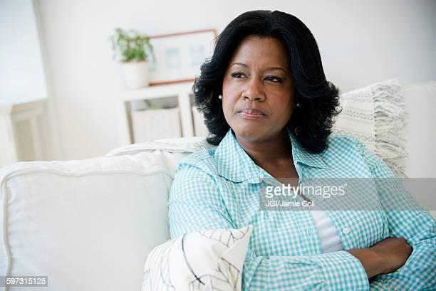 Unhappy Black woman sitting on sofa