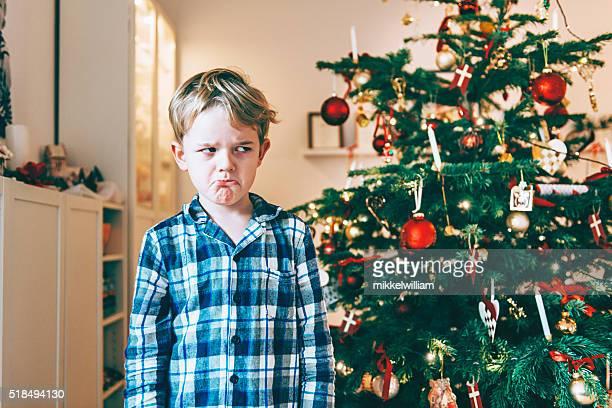 Malheureux garçon se tient avant Noël arbre et constitue un visage