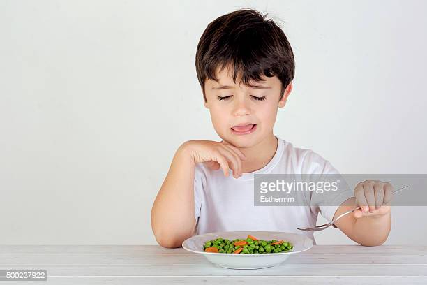 Unhappy Caucasian boy eating vegetables