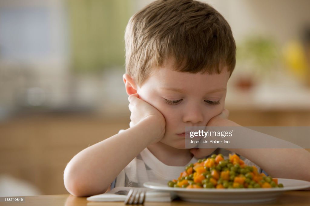 Unhappy Caucasian boy looking at dinner
