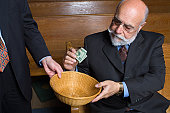 Senior male looking unhappy about making a donation to a church offering basket  - See lightbox for more