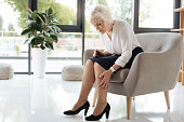 Feeling tired. Unhappy cheerless aged woman sitting in the armchair and looking at her legs while feeling tired after a difficult working day