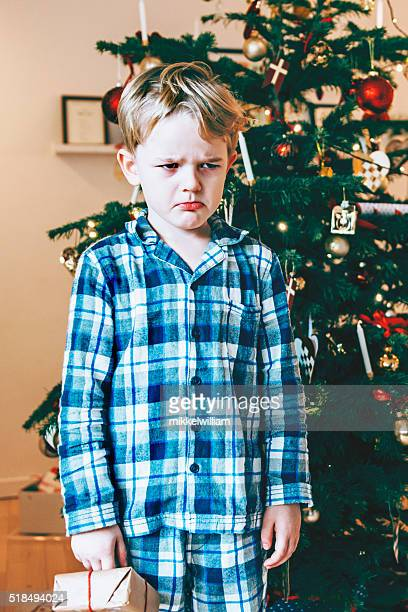 Unhappy child in pajamas stands before christmas tree with present