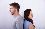 Unhappy Couple Standing Back To Back On Grey Background