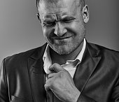 Unhappy depressed bald angry business man pulling the shirt collar with very bad emotions in office suit on grey studio background. Closeup portrait. Black and white
