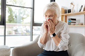 Catching a cold. Unhappy moody elderly woman holding a paper tissue and sneezing while having a cold