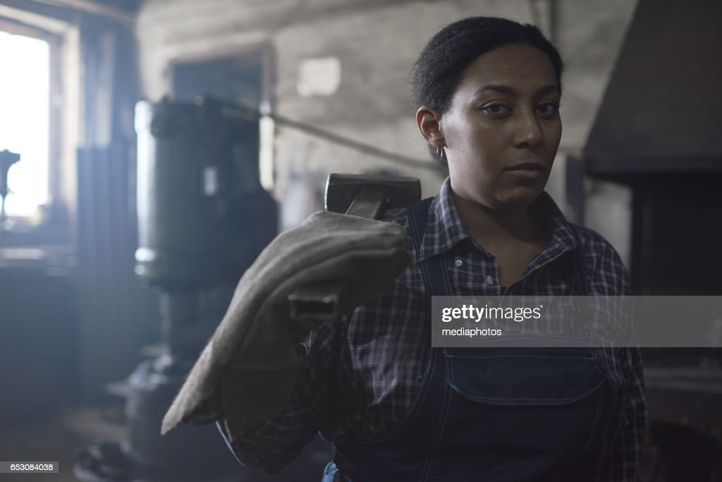 Unhappy female blacksmith : Stock Photo
