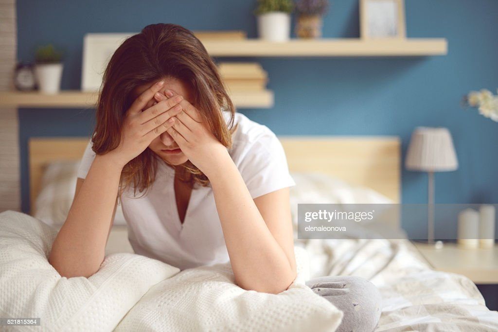 Unhappy girl in a bedroom : Stock Photo