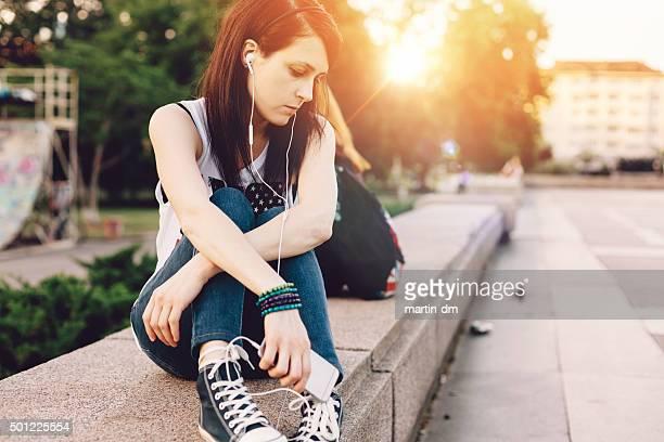 Triste petite fille écoute de la musique dans la ville