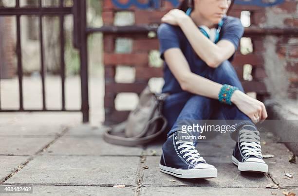Triste joven sentada en la planta baja