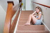 Unhappy Girl Sitting On Stairs At Home