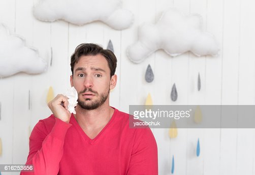 Unhappy ill man standing against cloudy background : Foto de stock