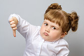 Unhappy little girl showing thumb down gesture isolated