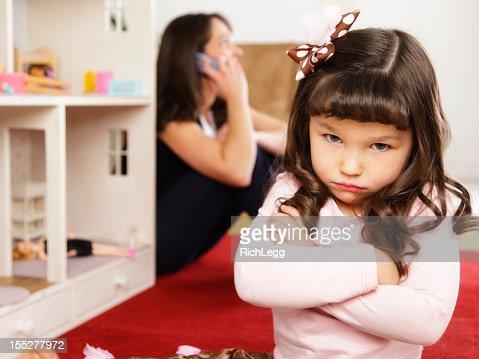 Infeliz niña con casa de muñecas
