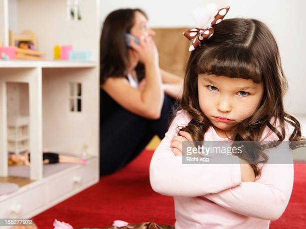 Unhappy little Girl with Dollhouse