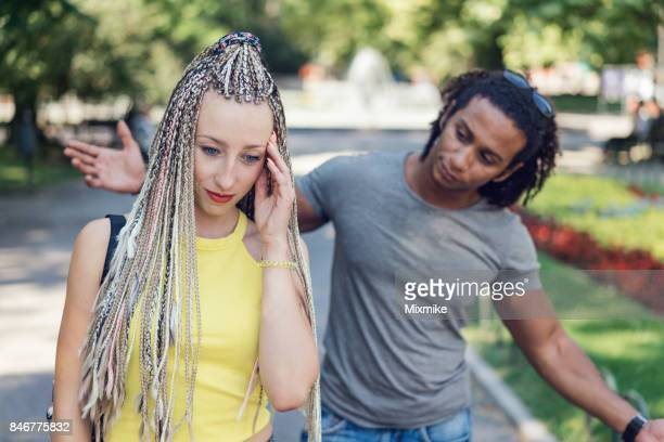 Unhappy looking woman holding her forehead and going away from her boyfriend