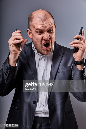 Unhappy loud crying anger business man talking on two mobile phones very emotional in office suit on grey studio background. Closeup : Stock Photo