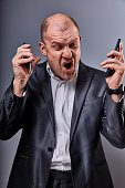 Unhappy loud crying anger business man talking on two mobile phones very emotional in office suit on grey studio background. Closeup portrait