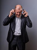 Unhappy loud crying anger business man talking on two mobile phones very emotional in office suit on grey background. Closeup portrait
