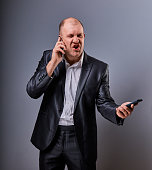 Unhappy loud crying angry business man talking on mobile phone very emotional in office suit on grey background. Closeup portrait