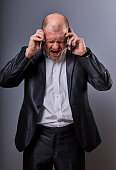 Unhappy loud crying angry business man talking on mobile phone very emotional wide opened mouth in office suit on grey background. Closeup portrait