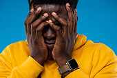 Feeling frustrated. Close up portrait of upset guy in yellow hoodie hiding face under arms. Isolated on blue background