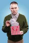 An unhappy man opening a Christmas gift