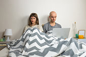 Man and woman sit in modern bedroom after quarrel or dispute, girl depressed or sad, male with laptop computer